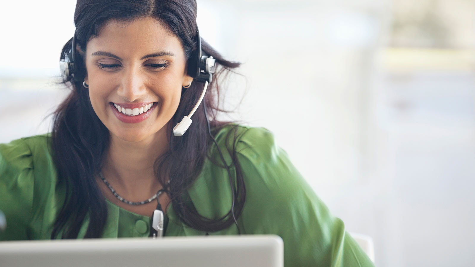 Woman wearing headset looking at laptop.